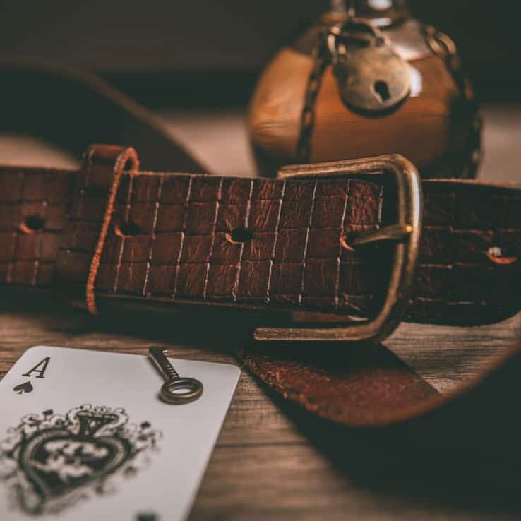 brown leather belt next to playing card and candle